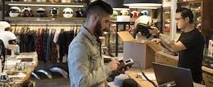 Man using credit card reader at counter in motorcycle shop