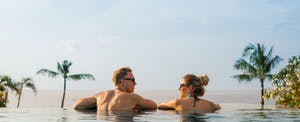 Couple relaxing in a pool overlooking an ocean view