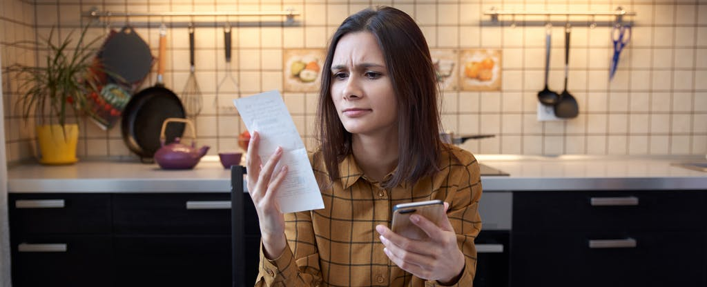 Woman sitting at a table looking at papers and a calculator