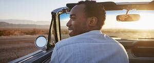 Rear View Of Man On Road Trip Driving Convertible Toward Sunset