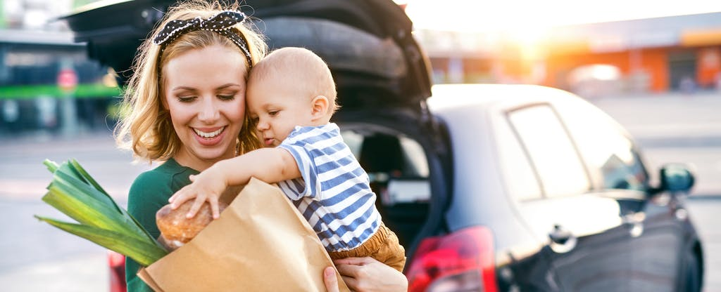 Woman holding her baby while loading groceries into her car