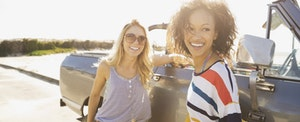 Two female friends standing by car