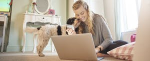 Young woman with her dog using her laptop on bedroom floor