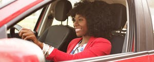 Smiling young woman driving a red car