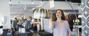 Woman checking price tag on lamp in home furnishings store