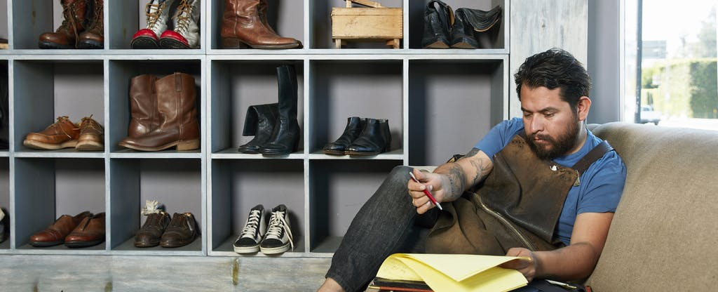Male cobbler in shoe shop sitting on sofa doing paperwork