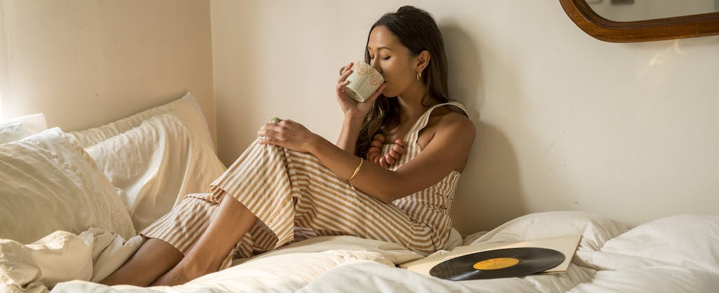 A young woman engages in JOMO while drinking coffee from cup in bed