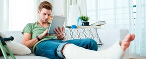 A young man with a broken leg sits on a couch at home, using a tablet to tally up his medical bills to see if he'll be eligible for the medical expense deduction.