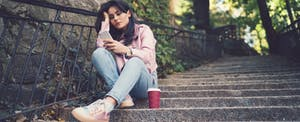 Unhappy young girl sitting on steps outside and texting