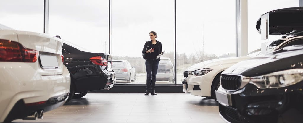 Woman looking at cars in a dealership