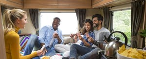 Group of friends having fun and playing cards in an RV.
