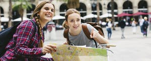 Two young female travelers reading a map