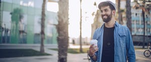Young man standing on the street holding coffee cup
