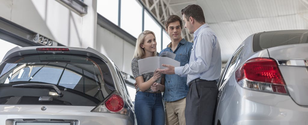 Couple shopping for a car and looking over terms with the dealer
