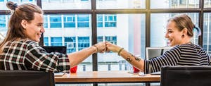 Young hipster couple fist bumping in victory after they learned about filing state taxes for free.