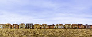 Houses in a row with a field in the foreground. Learn the average credit score to buy a house.