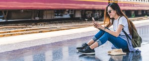 Young woman at train station using smartphone