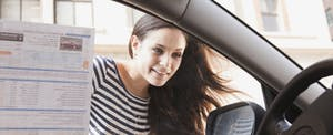 Woman looking into the window of a car with sale information on the window