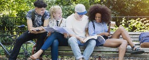 College students hanging out studying on park bench