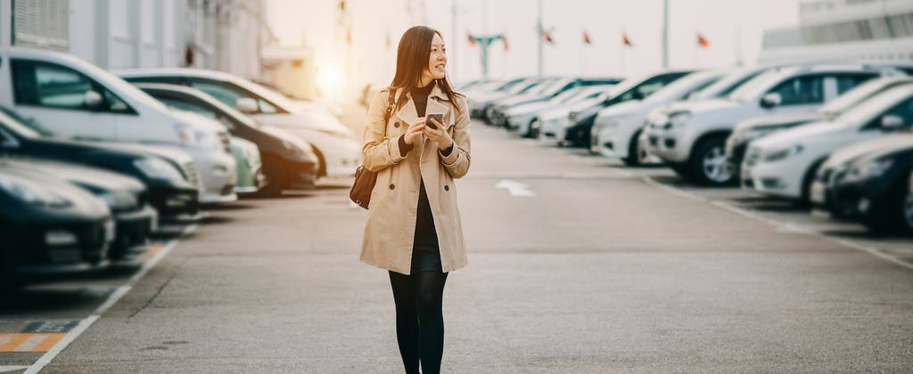 Young woman holding cell phone and walking in parking lot