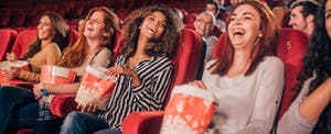Happy young women eating popcorn and smiling in the cinema