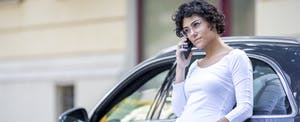 Woman leaning on her car and making a phone call