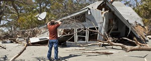 Man standing in front of his collapsed home, holding his head in his hands, may be able to take a casualty-loss deduction on his federal income taxes.