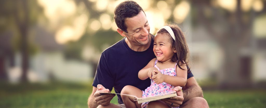 Smiling father with child contemplates whether he needs credit insurance