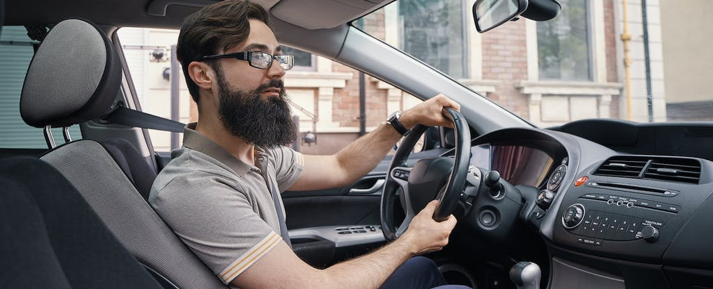 Young bearded man driving his car and smiling
