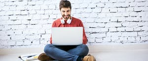 Male student sitting on floor with notebook and laptop studying