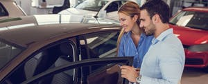 Smiling young couple looking for a new car to buy at car showroom.