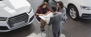 Couple signing the documents to buy a new car at a dealership