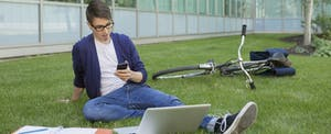 College student studying and texting on campus lawn