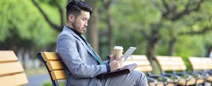 A young businessman is drinking coffee and working on a digital tablet in a public park.
