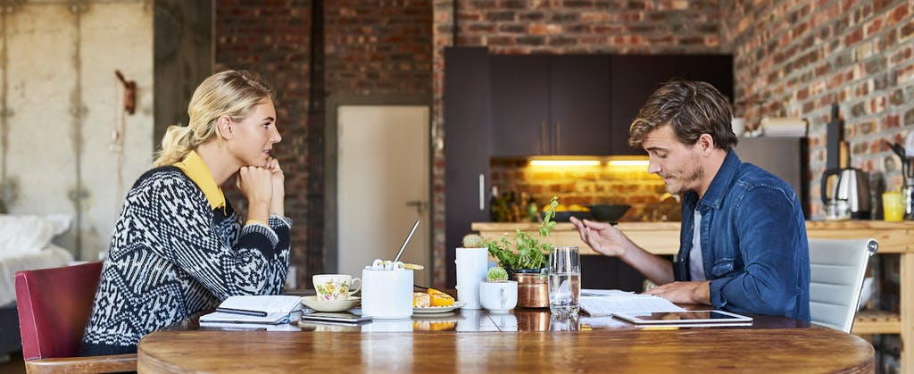 Couple working on their tax return on opposite sides of the kitchen table, trying to decide if they should use the married filing separately tax status.