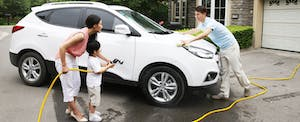 Parents and son washing their car in their driveway
