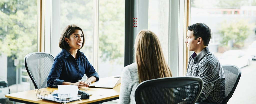 Smiling businesswoman in discussion with clients at office