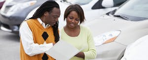 African American couple shopping for new car at dealership
