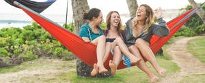 Three female friends in hammock together in tropical location