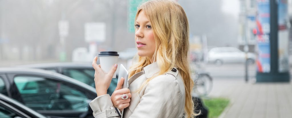 Young woman in city holding coffee and digital tablet
