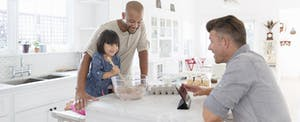 Male same sex couple with adopted toddler daughter baking in kitchen
