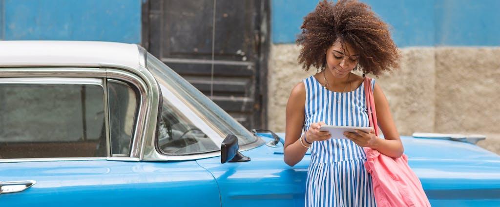 Woman looking at digital tablet, leaning against vintage blue car
