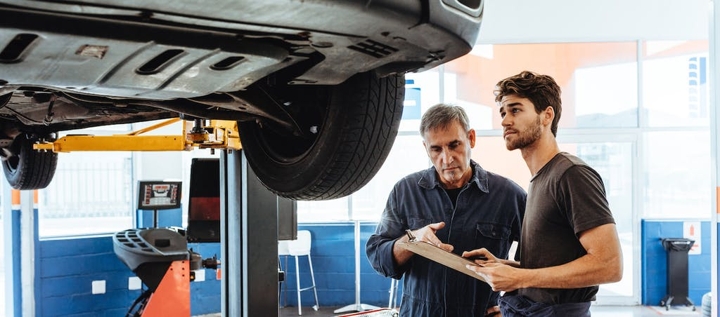 Middle-aged mechanic holding clipboard and discussing auto repair financing with young man