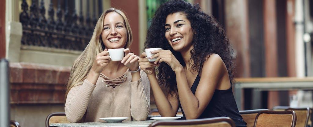 Two female friends having coffee at a sidewalk cafe