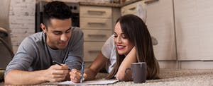 Young couple lying on the floor, drinking coffee and planning the best way to pay off their credit cards