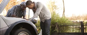 Two men outside looking at car motor