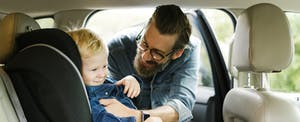 Man putting his son into a carseat