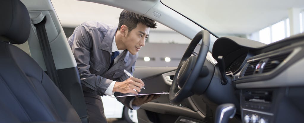 Man looking at a car and taking notes on a clipboard
