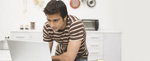 Man using a laptop on a kitchen counter
