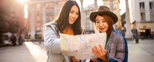 Two smiling young women reading a map while traveling in Italy